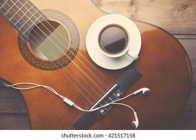cup of coffee, guitar and earphone on wooden background