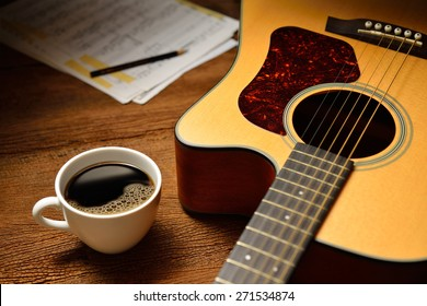 Cup of coffee and guitar on wooden table