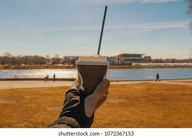 Cup of coffee in hand on the background of the river