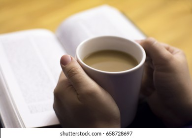 Cup of coffee in hands, reading bible. Selective focus