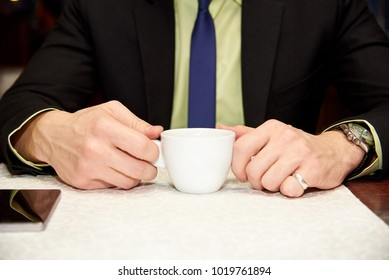 A cup of coffee in hands of a stylish businessman in a suit at the table