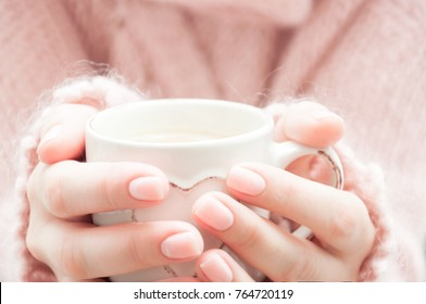 Cup of coffee in hands of a woman. Woman in a fluffy soft pink sweater with a cup of coffee in hand