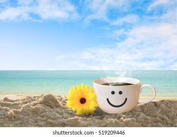 cup of coffee with happy face on sand beach over blue sky and sea. concept relax travel in holiday