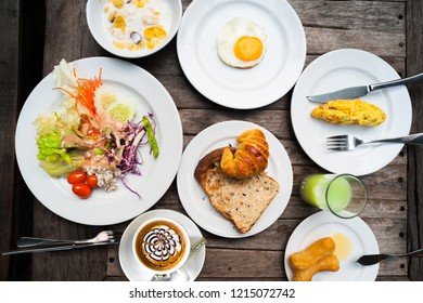 Cup of coffee and healthy breakfast and fried egg on old wooden table at the outdoor. Salad, deep-fried dough stick ,bread, Croissant and omelet
