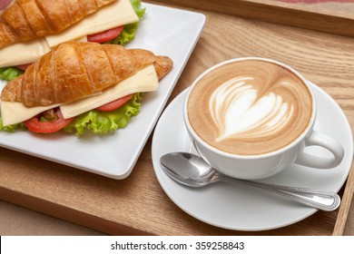 A cup of coffee with heart latte art on top and croissant cheese sandwiches