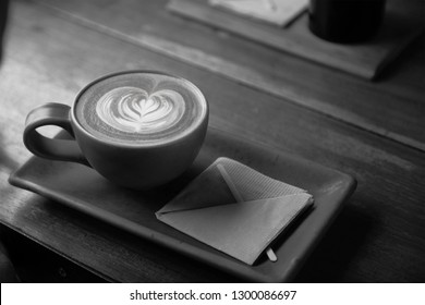 A cup of coffee with a heart latte foam art on top, sitting on a rectangular saucer and on a wooden table, in black and white, monochrome.