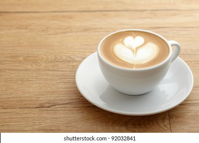A  cup of coffee with heart pattern in a white cup on wooden background