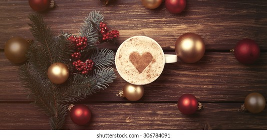 Cup of coffee with heart shape and christmas toys on wooden background.