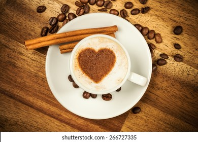 Cup of coffee with heart shape on foam served in porcelain saucer on wooden table. Shot from aerial view