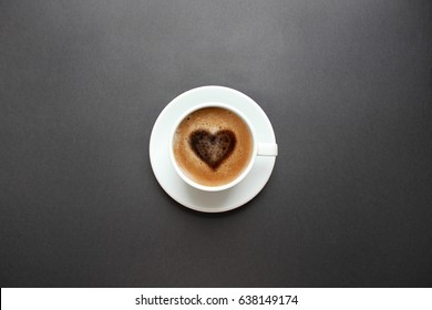 Cup of coffee with heart shape on black background. Top view with copy space.
