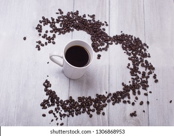Cup of coffee with heart shaped coffee beans surround.