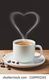 Cup of coffee with heart shaped smoke on rustic wooden table