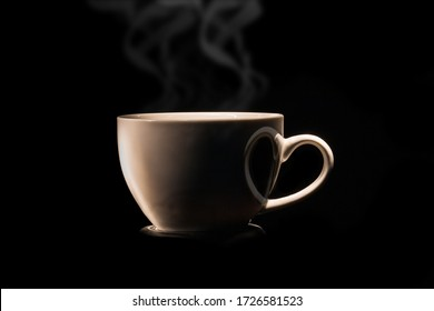 A  Cup of coffee and heart-shape shadow with smoke on black background, drink concept