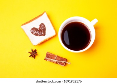 Cup of coffee and a heart-shaped nutella sandwich on a yellow background. Valentines day concept. Flat lay style