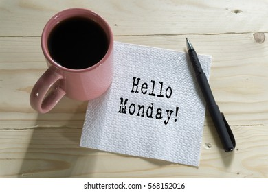 A cup of coffee with Hello Monday! written on tissue paper