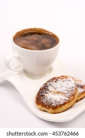 Cup of coffee with homemade donuts with powdered sugar