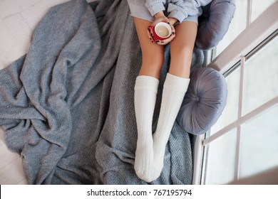 Cup of Coffee or hot Chocolate and Female Feet with Socks on a Gray Wool Blanket - Image