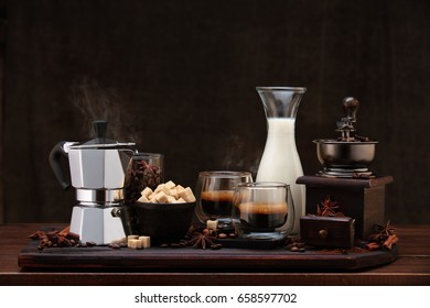 Cup of coffee and coffee ingredients on wooden table  with cinnamon and anise stars.