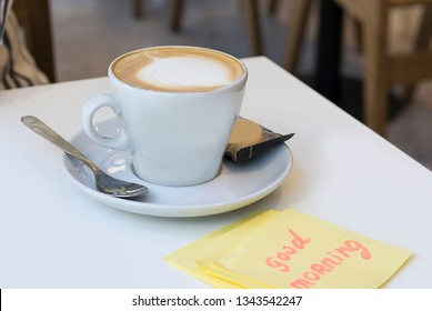 a cup of coffee and an inscription  with good morning on a sticker