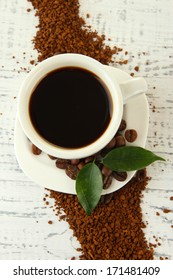 Cup of coffee with instant coffee on wooden background