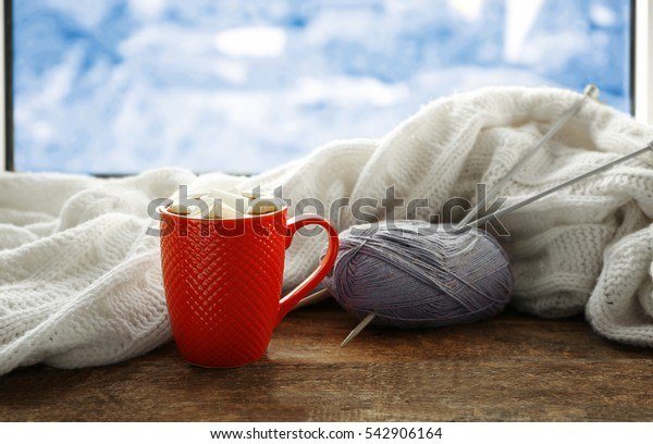 Cup of coffee and knitting on windowsill