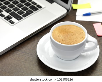 a cup of coffee and a laptop on a dark wooden desk