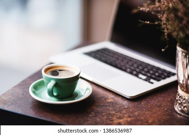 Cup of coffee and laptop on vintage iron table.