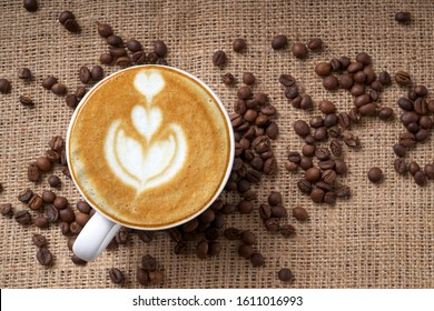 Cup of coffee latte art and coffee beans good essentials