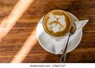Cup of coffee latte with latte art of a bear holding a love heart, on the wooden table.