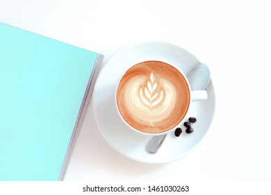 a cup of coffee with latte art and blank book color pastel blue on white background