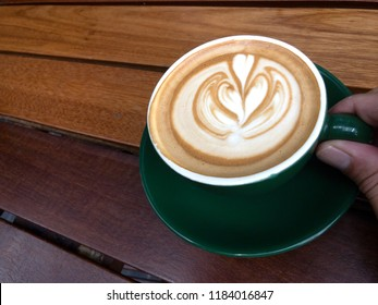 Cup of coffee with Latte art in a green mug