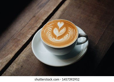 Cup of coffee latte art on wooden table