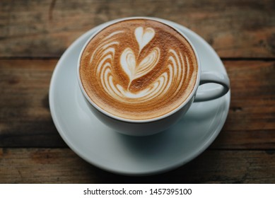 Cup of coffee latte art on wooden table background