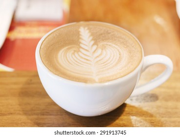 Cup of coffee latte art on wood table