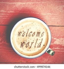 Cup of coffee latte, cappuccino on a pink wood table. Words welcome world written on a coffee top.
