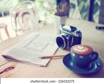 cup of coffee latte and classic camera  in coffee shop vintage color