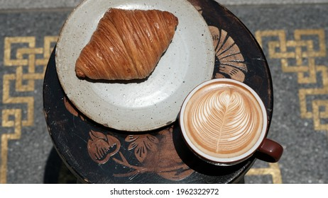 cup of coffee latte with croissant