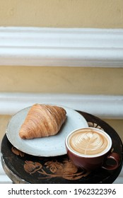 cup of coffee latte with croissant, yellow background for text