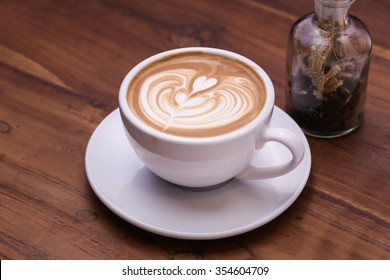 A cup of coffee latte with heart pattern in a white cup on wooden background