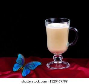 cup of coffee latte on red silk and blue morpho batterfly. copy spaces