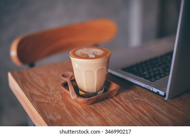 cup of coffee latte on the wood texture   in vintage color tone