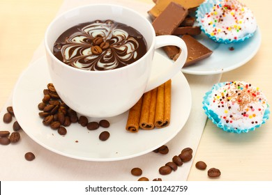 cup of coffee with lipstick, mark beans, cinnamon sticks on wooden table