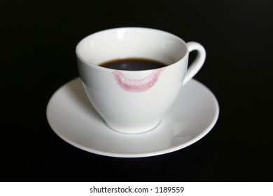 a cup of coffee with lipstick mark with dark background