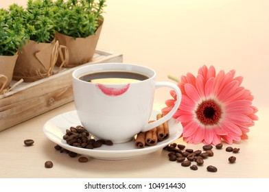 cup of coffee with lipstick mark and gerbera beans, cinnamon sticks on wooden table