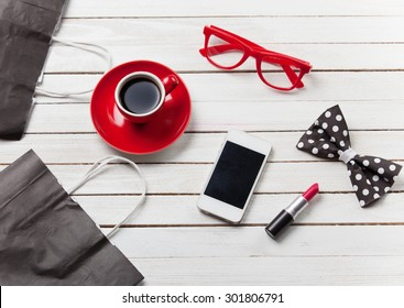 Cup of coffee with lipstick  shopping bags and mobile phone on the wooden background