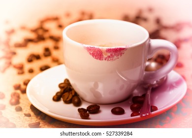 cup of coffee with lipstick traces and coffee beans around