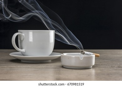 Cup of coffee and lit cigarette burning in ashtray