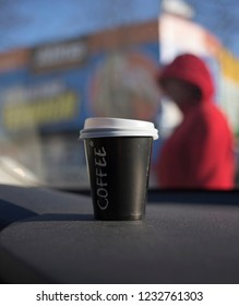 Cup of coffee is located on car console. The background is blurred.