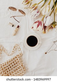 A cup of coffee lying on bed with white sheets, tulips, red lipstick, glasses, little purth and necklace. Flat lay, top view. Fashion, lifestyle, feminine concept.
