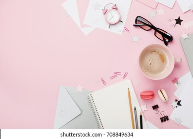 Cup of coffee, macaron, alarm clock, office supply and clean notebook on pink pastel table top view. Flat lay. Beautiful morning breakfast. Fashion woman blogger working desk.
